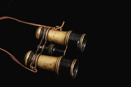 Vintage metal binoculars with a leather strap on a black background