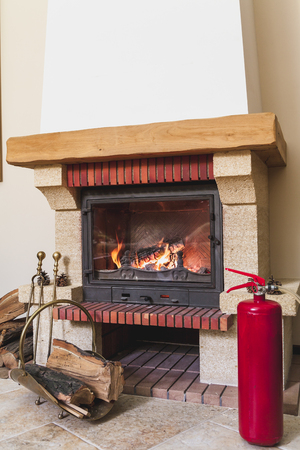 correct work of a modern fireplace. In front of the fireplace there is a red fire extinguisher, a drifter and a set of brass tools Banco de Imagens
