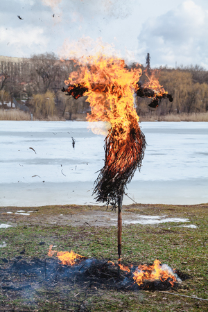 Slavic holiday of the end of winter. A large Shrovetide doll from straw burns on the river bank. Black smoke is visible Archivio Fotografico