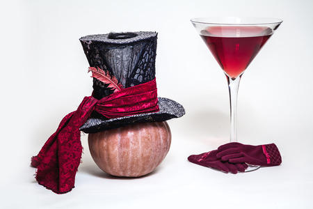 Magic still life. Big cylinder hat on a ripe pumpkin and a huge martini glass with wine on a white background Stock Photo