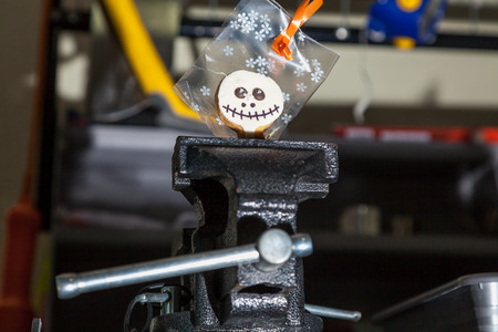 Halloween in the workshop. Cookies for Halloween in a transparent package clamped in a vice in the tool shop Stock Photo