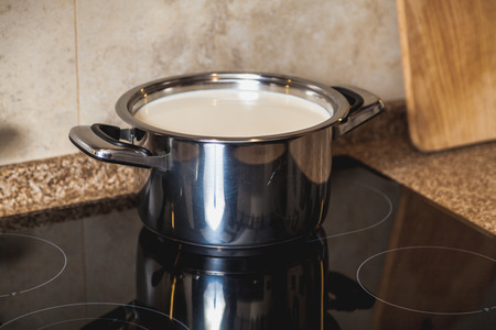 Boil milk. Metal pan with milk stands on a modern black electric stove