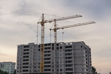 Perfectionism on the construction site. Two yellow cranes build a tall multi-storey house against a cloudy sky background