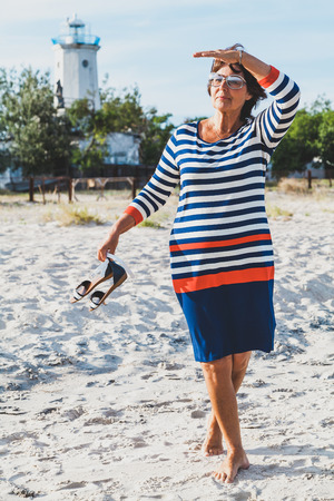Beautiful elderly woman in striped dress on beach at background of old lighthouse