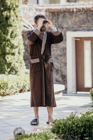 Summer morning in the courtyard. A man with a beard in a brown coat went out into the courtyard of the estate in the early morning and looks through binoculars