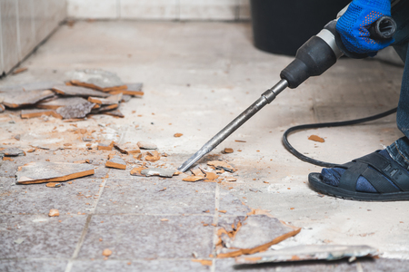 construction puncher with a long flat peak destroys the floor tiles in a small room. Close-up