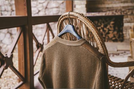 Autumn story. A woolen knitted jacket hangs on a hanger on the back of a wicker chair on the veranda Standard-Bild
