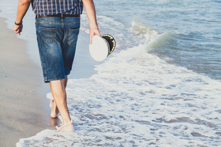 Man in shorts walking on sea beach summer evening Stockfoto
