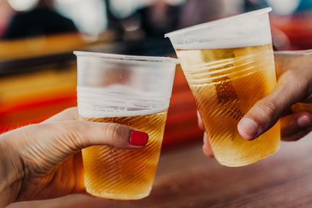 Beer appointment. A hand with a woman with a manicure holds a plastic glass with beer. The second glass in the man's hand Stockfoto