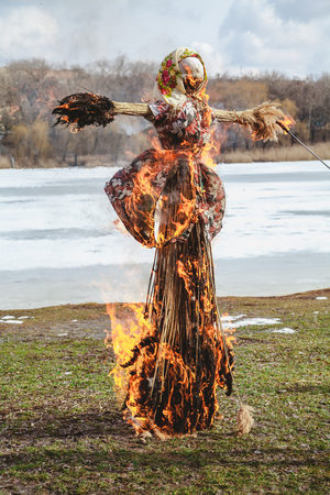 Slavic holiday of the end of winter. A large Shrovetide doll from straw burns on the river bank Archivio Fotografico