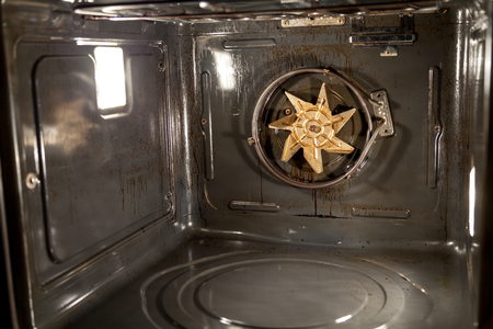 The angle of the metal walls inside the electric oven. A fan propeller is visible on the back wall