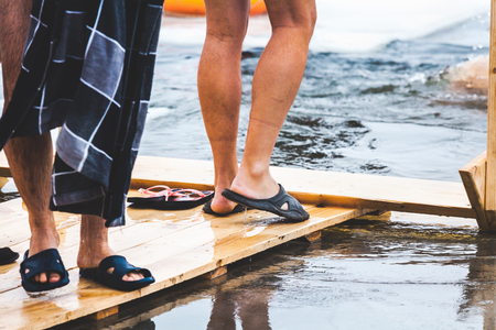 Men bare feet on the wooden platform in front of an ice-hole in a frozen pond in the winter feast of Epiphany