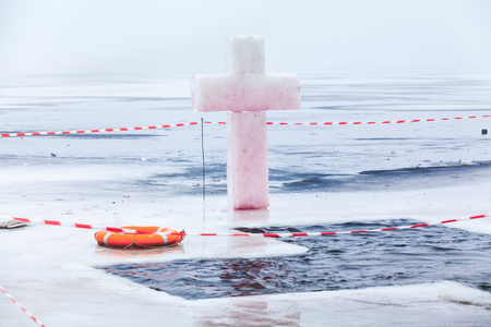 Ice cross hole and an orange life preserver at the celebration Epiphany overcast winter day Stockfoto
