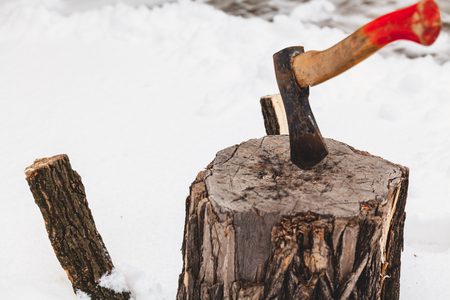 Harvesting of firewood in winter. The ax sticks out in a stump on white snow. Two halves of a split log stick out in the snow
