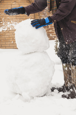 make a snowman. a man in ski gloves places a large snowball on a lower lump of a larger size Banco de Imagens