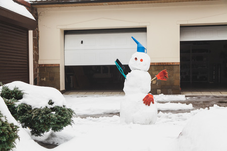 Snowman motorist stands in front of the garage. For decoration use a watering can, a brush and working gloves Banco de Imagens