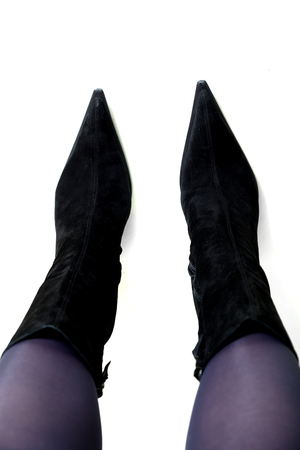 Slender female legs in fashionable black suede boots with narrow socks on a white background. View from above