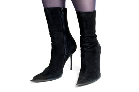 Slender female legs in fashionable black suede boots with narrow socks and high thin heel on a white background. Side view