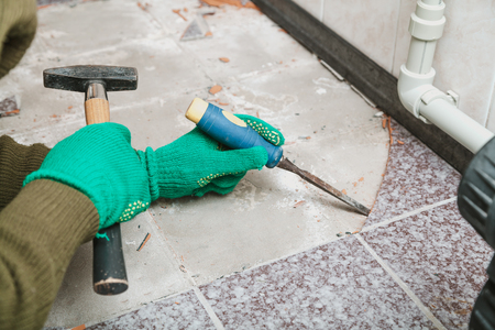 dismantling of tile. Hands in green working gloves undermine the tile with a chisel and a hammer Foto de archivo