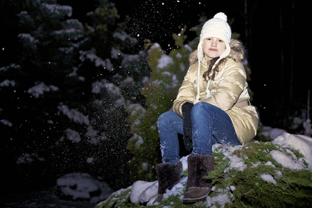 young girl in a yellow jacket sitting on a snowy branch of a Christmas tree