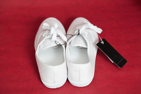 Two new white sneakers with laces stand on a red isolated background.