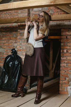Pretty slender blonde in glasses and leather boots stands on wooden boards in the attic against the brick wall
