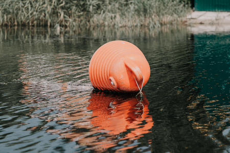 Safety on the water. A large orange buoy horizontally lies on the water of the Gulf of the River