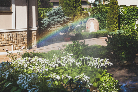 left half of the rainbow arc over the white colors of the host in the well-tended courtyard of the house on a summer day Stockfoto