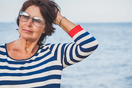 Pretty elderly woman in sunglasses on vacation at the seaside