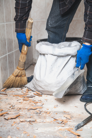 builder collects the pieces of floor tiles into a white bag in a small room close up