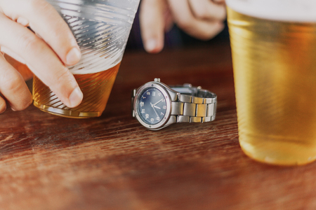 Wristwatches with a metal bracelet lie between two plastic glasses with beer. Incomplete glass in the man hand