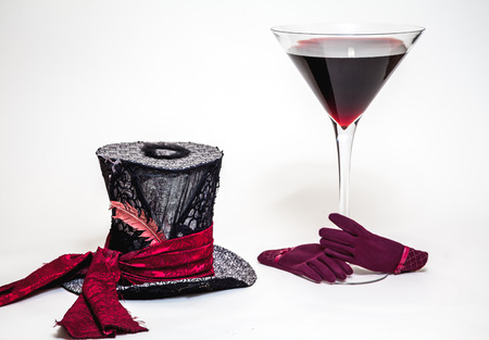 Magic still life. A big cylinder hat and a huge glass goblet with red wine on a white background. Near red women's gloves Stock Photo