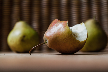Still life with pears. Two green pears lie on a wooden board. Nearby is the third pear on which bite marks are visible.