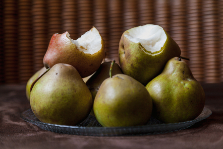 Still life with green pears. A group of appetizing green pears lies on a plate. On top are two pears with traces of human bites.
