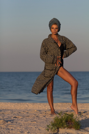 Woman model in turban and summer knitted coat standing and posing in full growth on sandy sea beach Foto de archivo