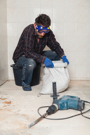 builder lifts a heavy white sack with construction debris in a small room close up