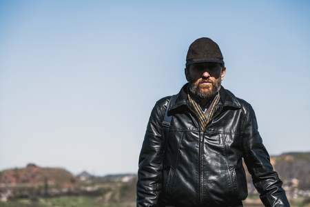 Spring and Terricons. A man with a beard in a cap and a leather jacket goes against artificial mountains and rivers