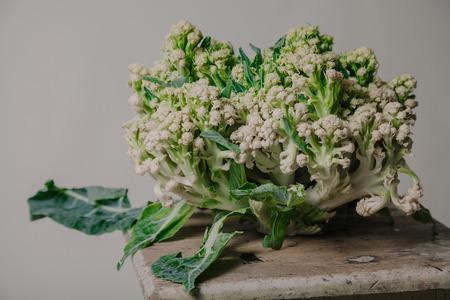 Autumn still life. Cauliflower head on a small wooden bench close-up