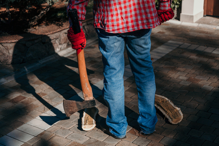 Dangerous shadow. A man in a red checkered shirt holds an ax in his hand in the yard. A deceptive shadow falls from him 版權商用圖片