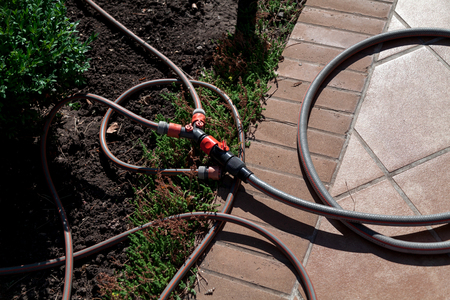 Plastic tee with adjustable water flow with rubber hoses lies on the edge of the garden