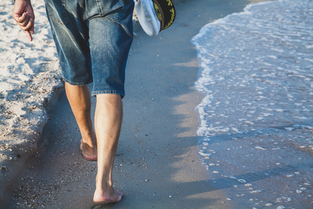 Man in shorts walking on sea beach summer evening Stockfoto