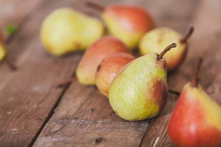 group of ripe pears lie on old planed wooden boards