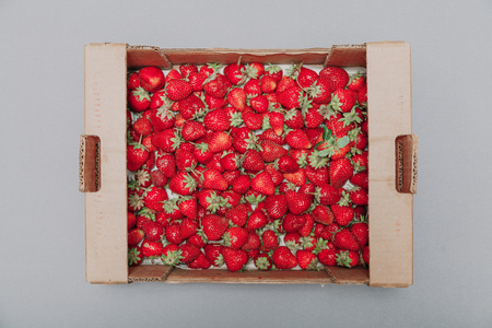 Strawberry harvest. Appetizing red strawberries with green tails lie in a cardboard box on a white background