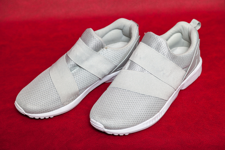 Two new light gray sneakers with a mesh top stand on a red isolated background.