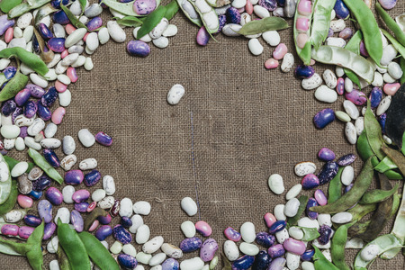 Pods and seeds of beans of different colors lie on the sacking along the edges. The middle is empty. View from above. Close-up