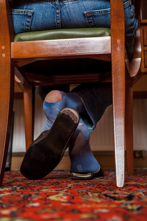 Holes in socks. A man sits on a wooden chair in the office in slippers on his both socks; you can see big holes sock, full of holes Imagens