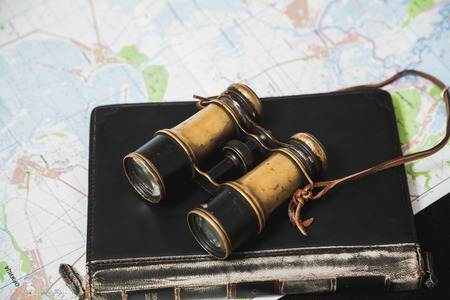 Vintage metal binoculars lie on a leather-bound notebook. The notepad lies on the topographic map