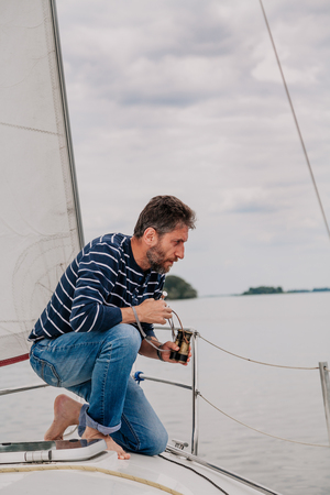 man with a beard in a striped sweater and jeans sits on the bow of a sailing yacht and looks overboard on a cloudy day.