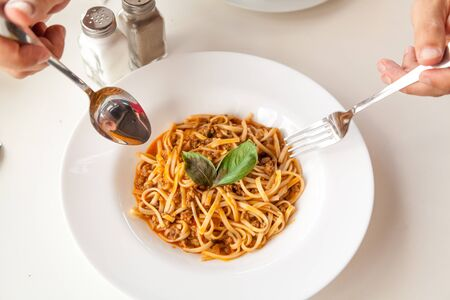 Hands holding a spoon and fork over appetizing spaghetti on a round plate decorated with green leaves close up.