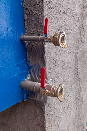 Two water fire hydrants of different diameters come out of the blue box against the gray wall